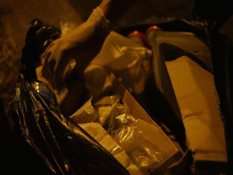 Eine Hand mit Plastikhandschuh greift in eine Mülltonne.