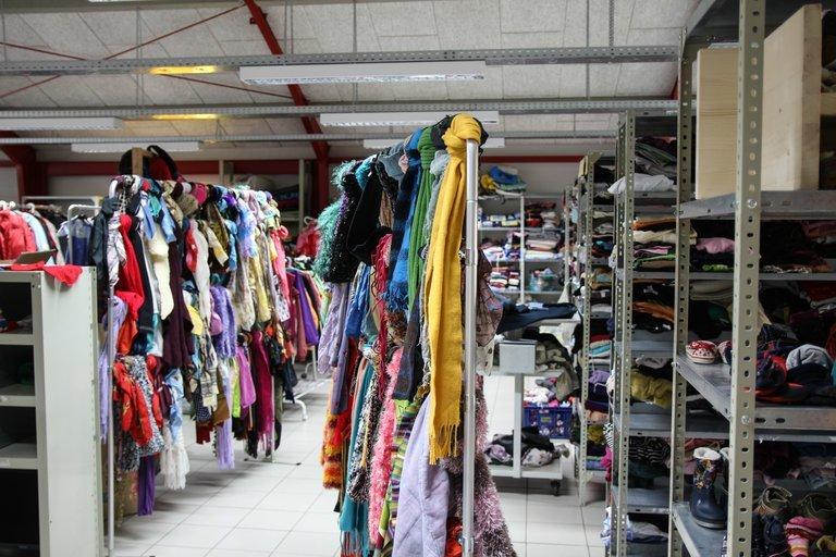 Blick in die volle Kleiderkammer. Mehre Regale voll mit Klamotten.