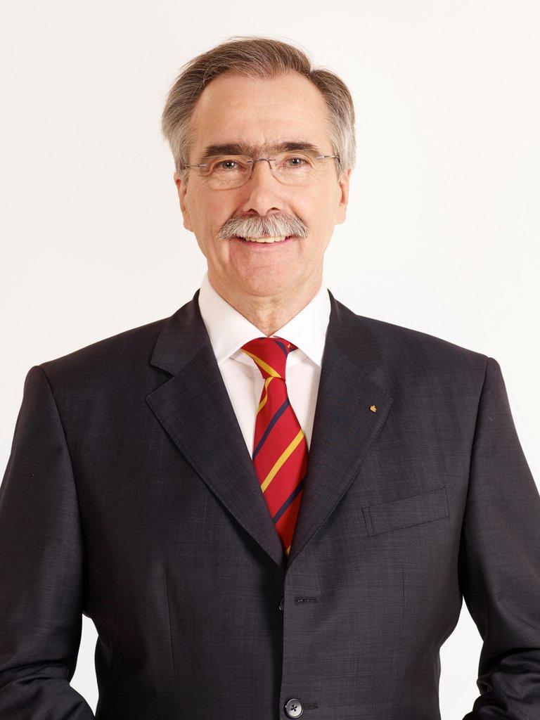 Hans Laven schaut in einem Anzug schick gekleidet in die Kamera