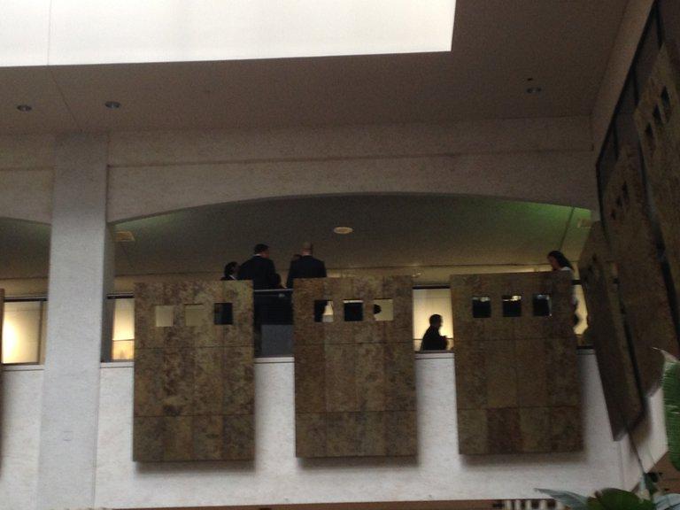 Männer stehen auf einer Empore um Tische herum