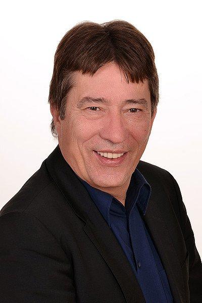 Peter Schneider trägt einen schwarzen Anzug, lacht in die Kamera