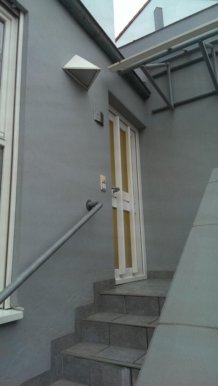 Eine Treppe führt zu einer Tür mit einem Klingelschild des Vereins.