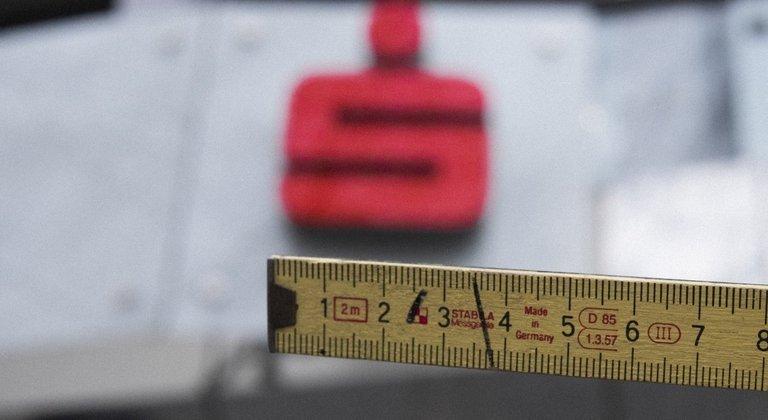 Ein Lineal wird unter ein Sparkassen Logo gehalten
