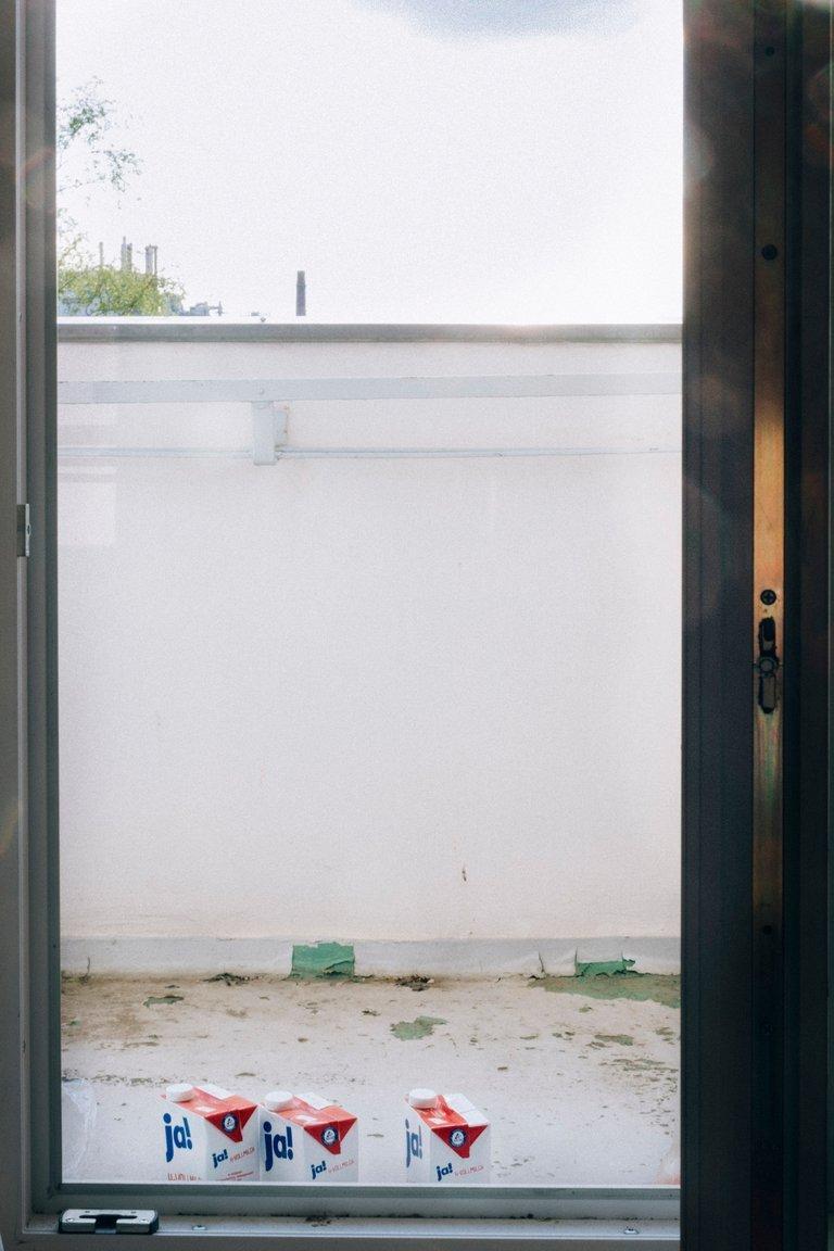 Drei H-Milch Packungen stehen auf dem Balkon von Miguel.