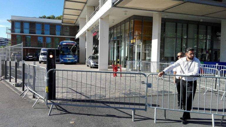 Absperrgitter vor einem Hotel. Zwei Männer bewachen den Eingang.
