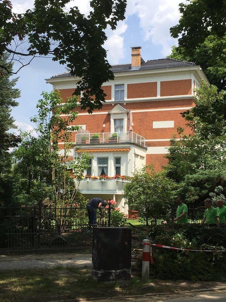 Blick auf die Front der Villa. Drei Gärtner arbeiten auf dem Grundstück.