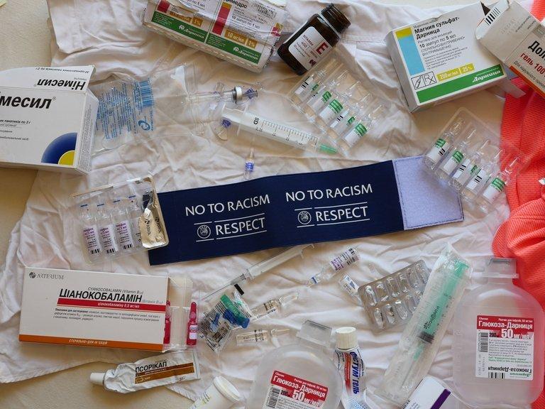 Alle Medikamente auf einem Tisch ausgebreitet. In der Mitte liegt die blaue Kapitänsbinde der Ukrainer