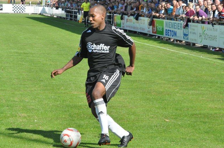 Marcus Storey im Trikot von Rehden. Er dribbelt mit dem Ball auf dem Fußballplatz. Im Hintergrund sieht man Zuschauer vom Spielfeldrand zuschauen.