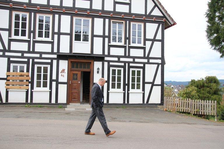 Der Bürgermeister schaut auf das Fachwerkhaus.