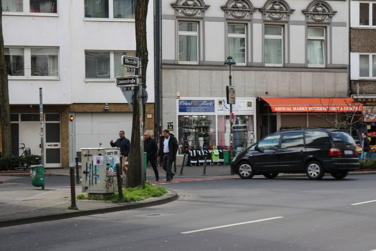 Drei Menschen laufen durch die Strae Im Hintergrund erkennt man einen trkischen Supermarkt