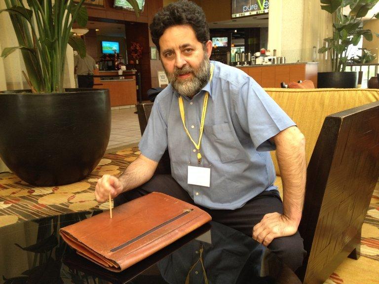 Ein Mann sitzt an einem Tisch, auf dem eine Ledertasche liegt