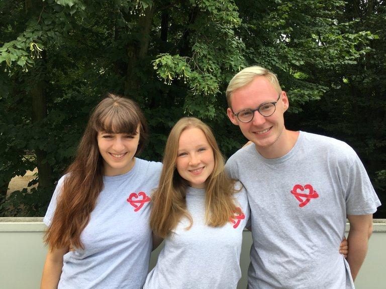 Frederike Booke und zwei Kollegen haben ein T-Shit an mit dem Logo ihres Projektes auf der Brust.