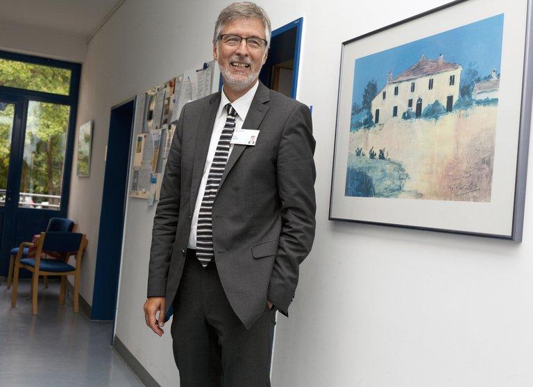 Psychiater Arno Deister steht im Klinikum Itzehoe vor einer Wand