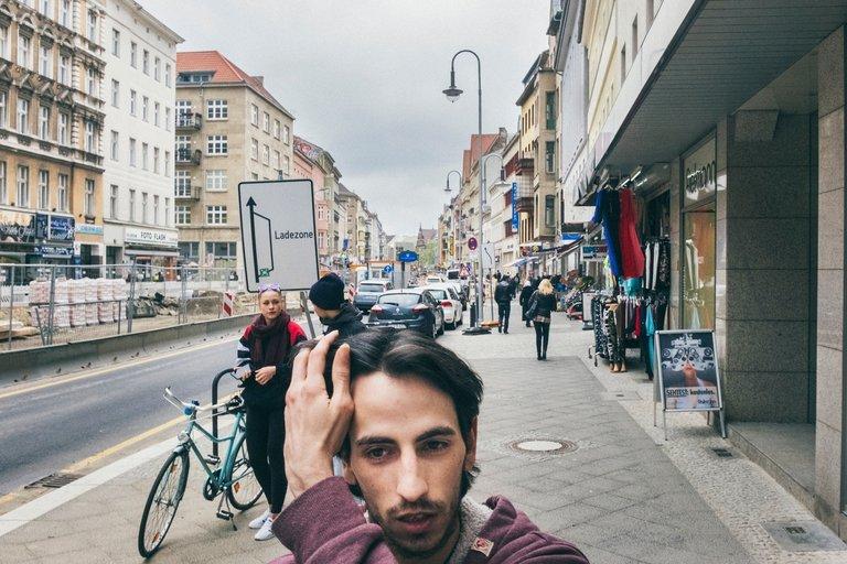 Miguel auf dem Rückweg vom Jobcenter auf der Karl-Marx-Straße. Im Hintergrund der Heimathafen, hier hat er im Saalbau in einer Maßnahme gearbeitet.
