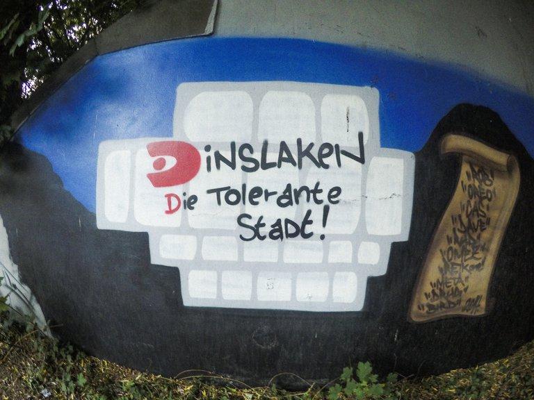 """Ein Graffiti auf einer Mauer in Dinslaken mit dem Schriftzug: """"Dinslaken — Die Tolerante Stadt!"""""""
