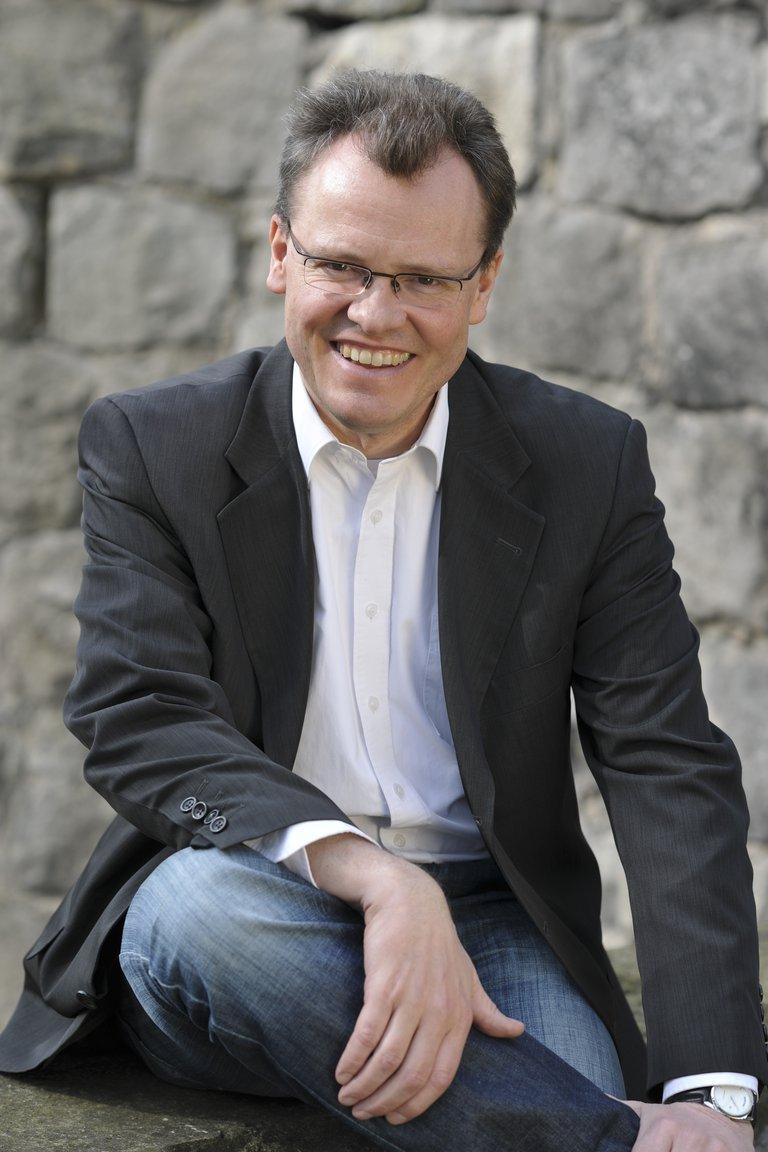Michael Heidinger, Mann mit Brille, sitzt und lächelt in die Kamera