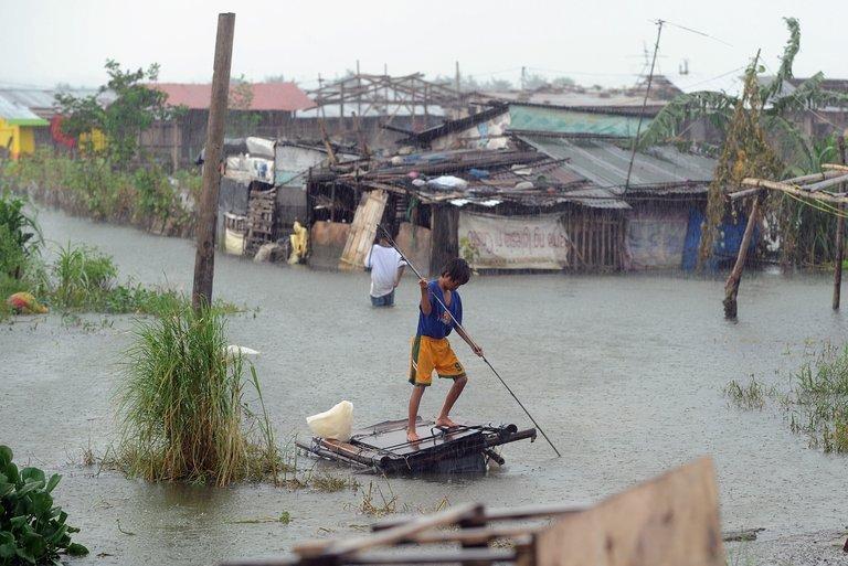 Ein Junge stakst durch einen überschwemmten Slum.
