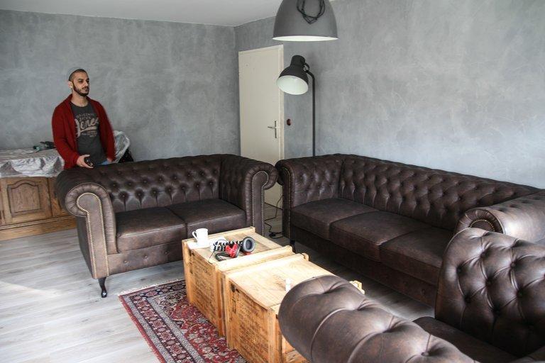 Jounes Al-Amayra steht in seinem Zimmer. Darin stehen zwei Leder Couches.