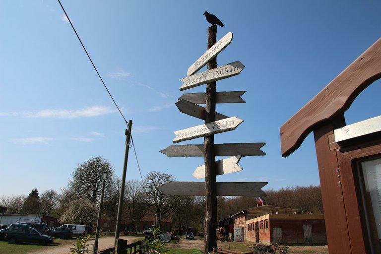 Ein Wegweißer aus Holz mit den Kilometerangaben zu verschiedenen Städten. Unter anderem nach Hitlers Geburtsort Braunau.