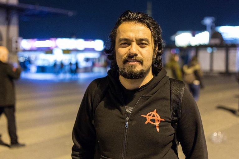 Ferat hat eine schwarze Jacke mit einem Anarchie-Logo auf der Brust an, schaut in die Kamera