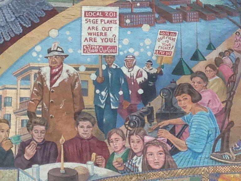 Ein Wandbild, auf dem eine Demonstration für höhere Löhne aus dem Anfang des 20. Jahrhunderts dargestellt ist.