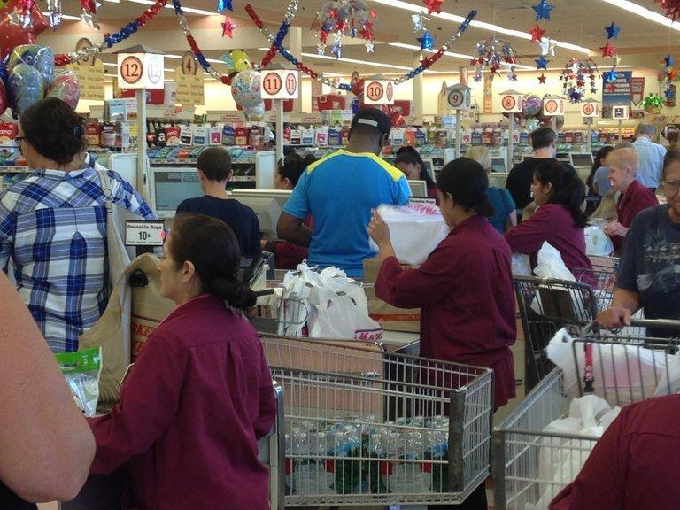 An Supermarktkassen packen Angestellte Tüten für dei Kunden ein.