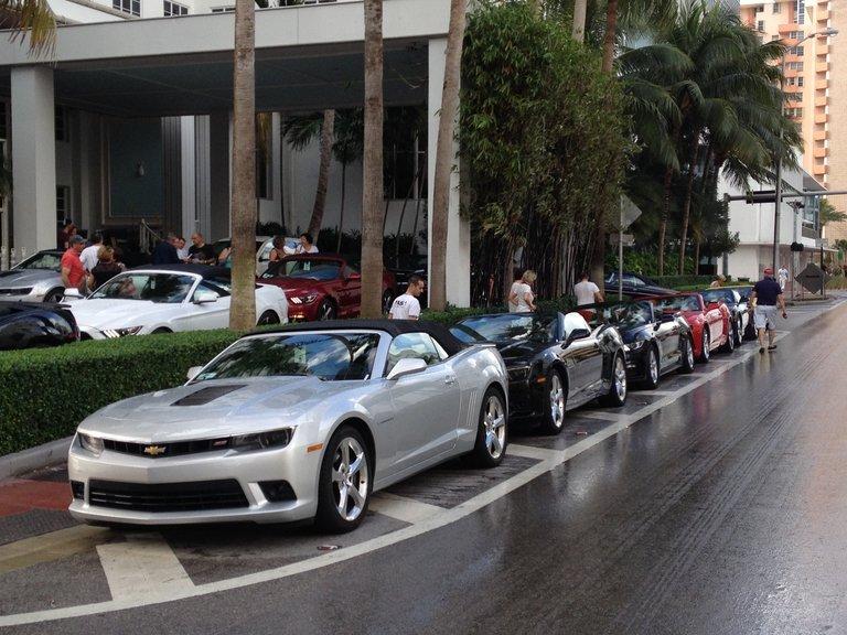 Sportwagen stehen am Strassenrand.