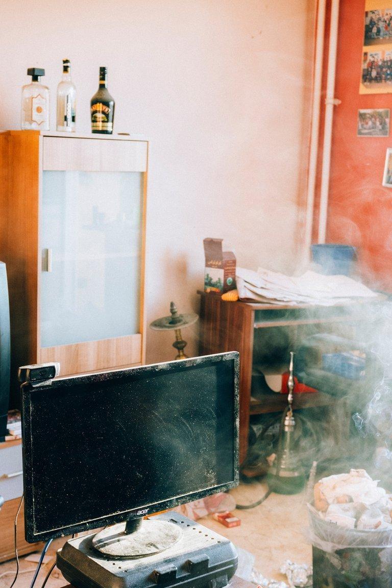 Der Computer auf einem Couchtisch, im Hintergrund der Schreibtisch mit Papieren, an der Wand alte Schulfotos.
