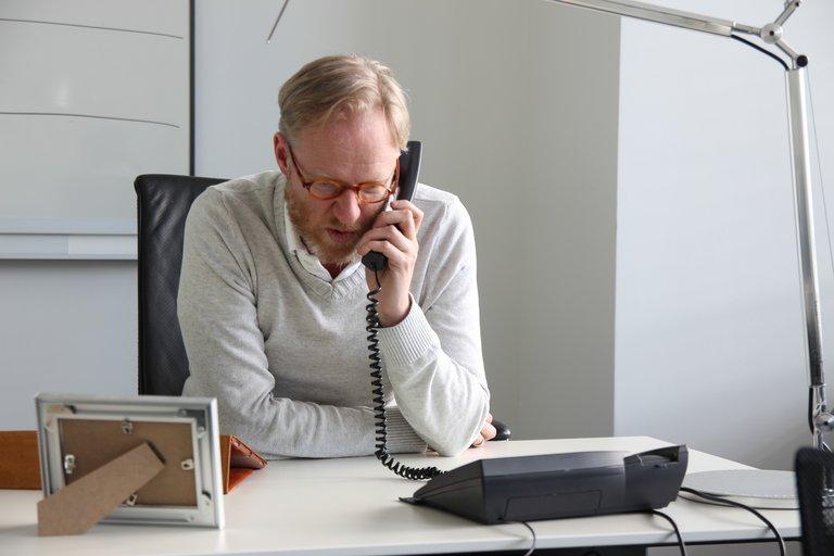 Vetterick sitzt an seinem Schreibtisch und telefoniert.