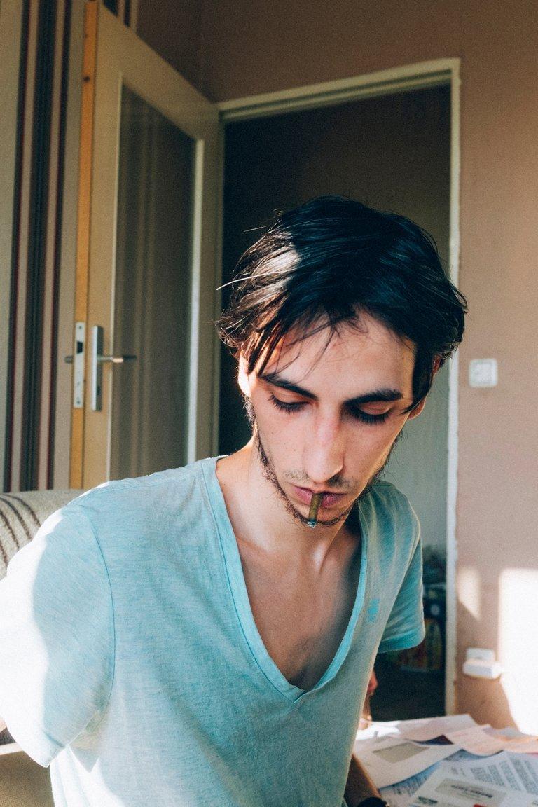 Miguel sitzt in seinem Zimmer und raucht eine Zigarette.