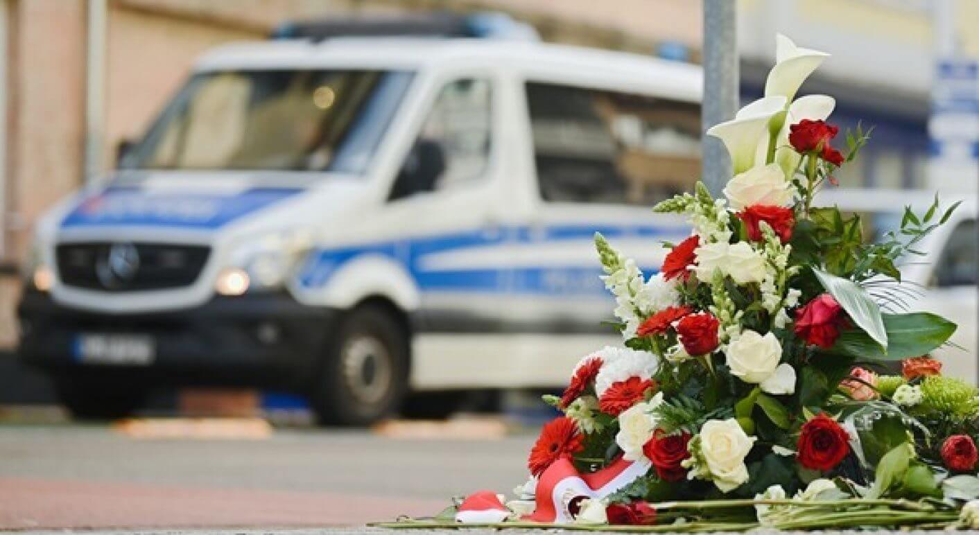 Anschlag in Hanau: Blumengesteck und im Hintergrund ein Polizeiwagen