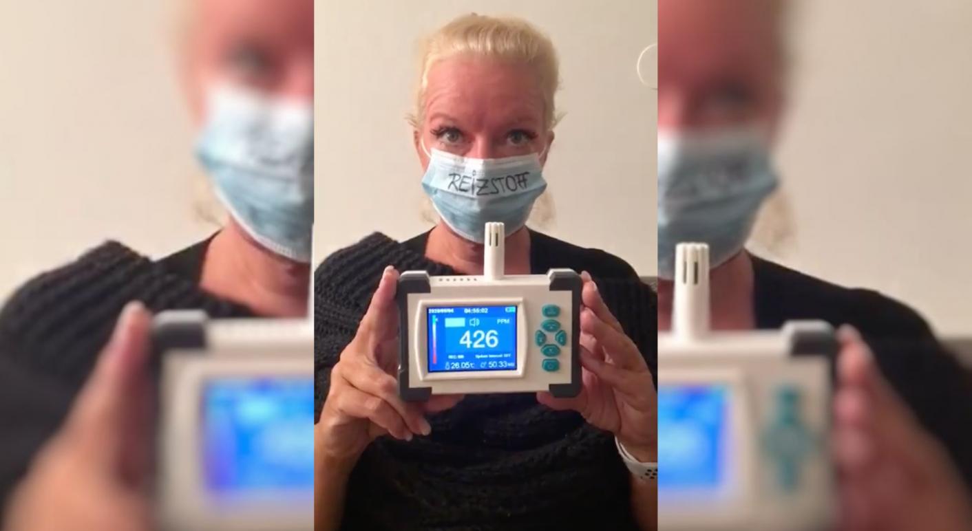 Eine Frau misst den CO2-Gehalt unter ihrem Mund-Nasen-Schutz. Doch die Messung ergibt keinen Sinn und das Gerät ist nicht dafür ausgelegt.