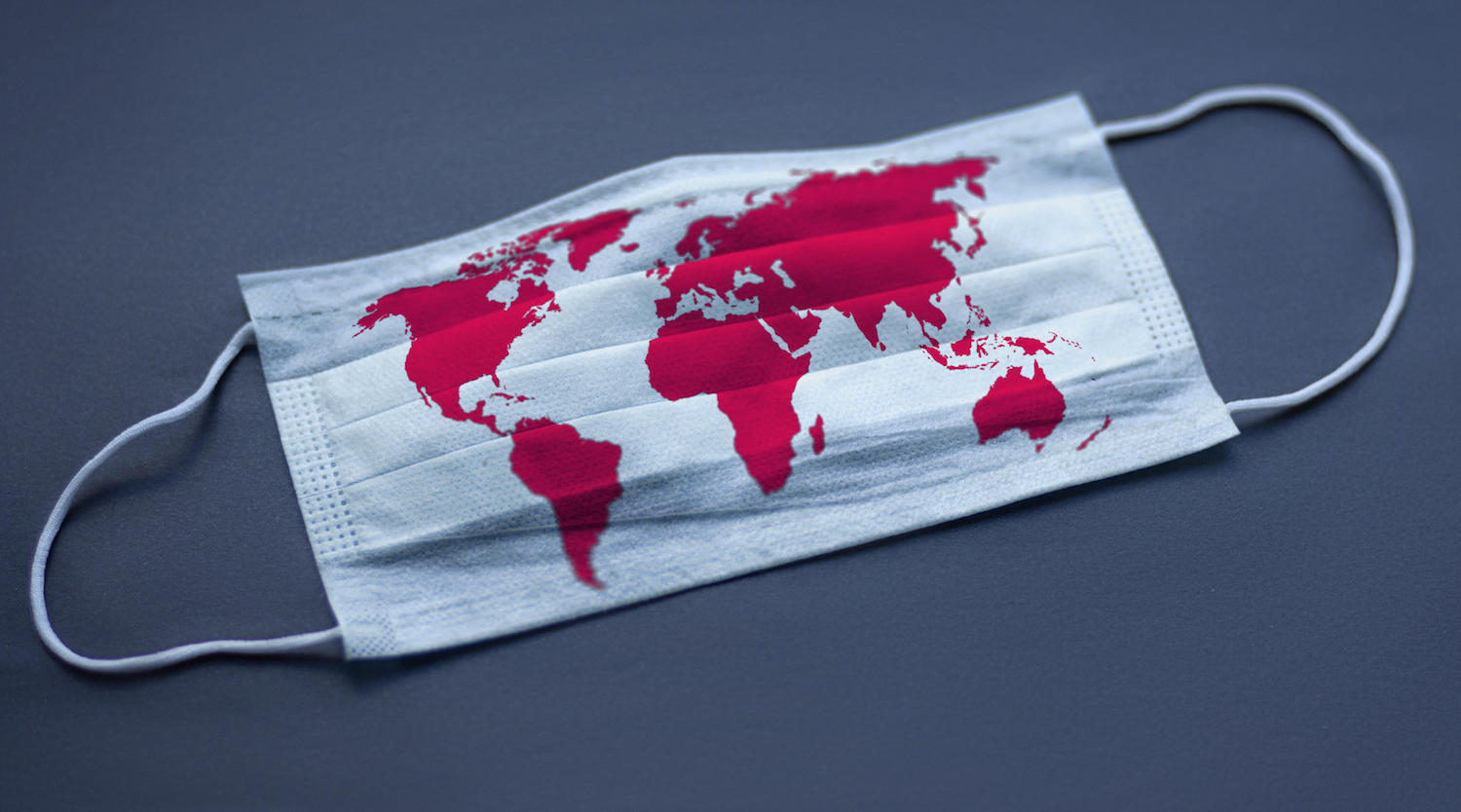 Ein Symbolbild zeigt eine Gesichtsmaske mit einer Weltkarte darauf